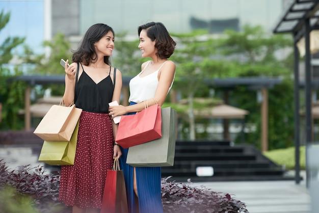 Ładne młode kobiety stojące na świeżym powietrzu po wspólnych zakupach i omawianiu nowości i plotek o zakupach