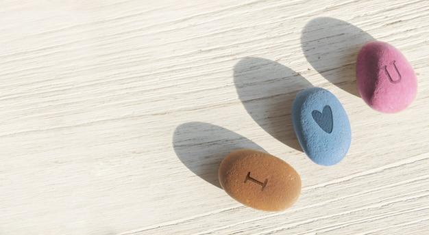 Ładne okrągłe kamienie z tekstem i love u na białym drewnie. koncepcja walentynki