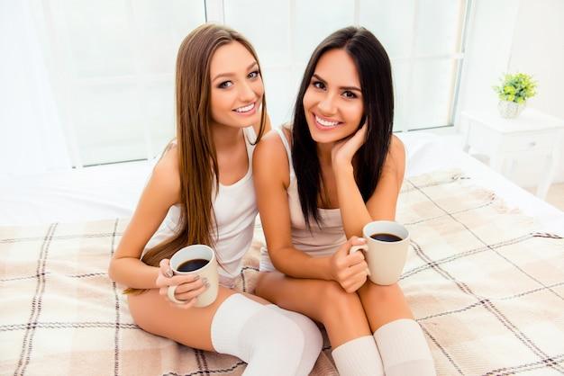 Ładne ploteczki pijące kawę i siedzące na łóżku