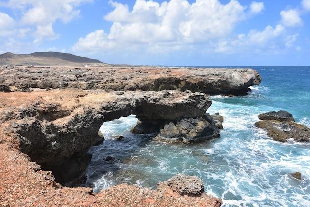 Ładne skaliste wybrzeże nad brzegami jasnoniebieskich wód arubańskich