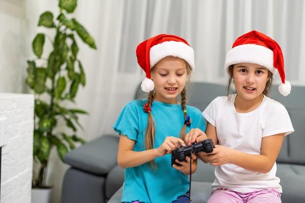 Ładne słodkie dziewczyny w czapkach świętego mikołaja siedzą grając w bitwę urządzenia wideo