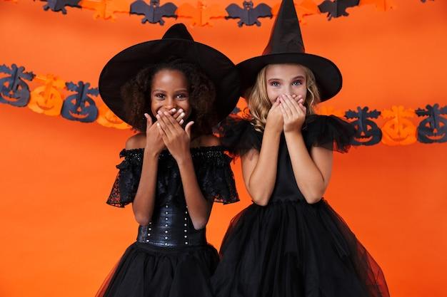 Ładne wielonarodowe dziewczyny w czarnych kostiumach na halloween, śmiejące się i zakrywające usta, odizolowane na pomarańczowej ścianie z dyni