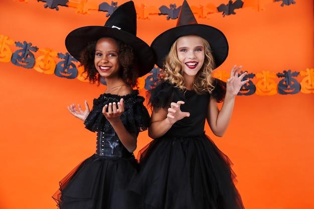 Ładne wielonarodowe dziewczyny w czarnych kostiumach na halloween, uśmiechnięte i wyśmiewane na tle pomarańczowej ściany z dyni