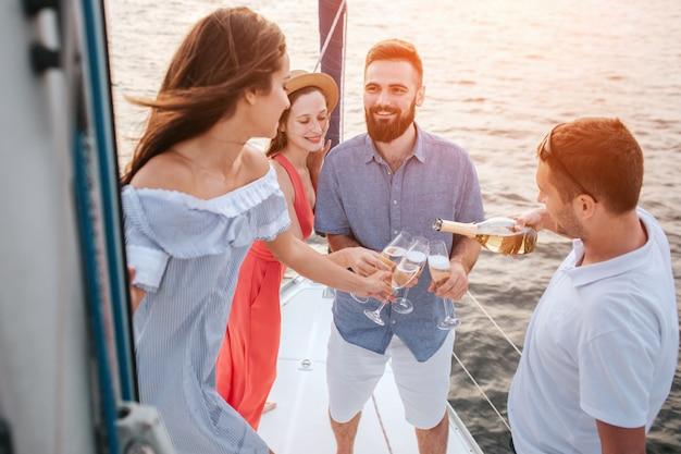 Ładne zdjęcie czterech osób stojących razem na jachcie. mężczyzna w białej koszuli nalewa szampana do szklanek. brunetka patrzy na innego mężczyznę.