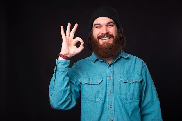 Ładne zdjęcie młodego, brodatego szczęśliwego mężczyzny, który uśmiecha się do kamery i pokazuje znak ok w pobliżu ciemnej ściany