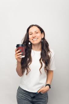 Ładne zdjęcie młodej uśmiechniętej kobiety patrzącej na aparat i trzymającej kubek gorącego napoju