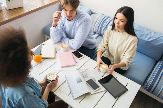 Ładne zdjęcie trzech studentów siedzących przy stole. na stole jest wiele urządzeń i notebooków. każdy z nich ma filiżankę kawy. cieszą się towarzystwem.