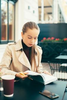 Ładne zdjęcie w kawiarni z kobietą, która pisze i organizuje swój czas przy stoliku na zewnątrz