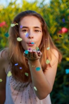Ładnej młodej kobiety podmuchowi confetti w parku na zmierzchu.