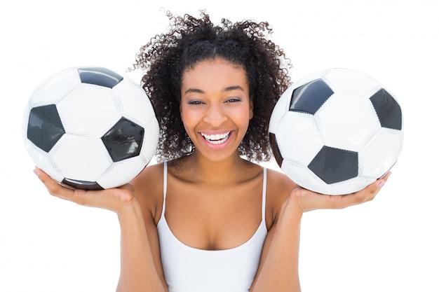 Ładni dziewczyny mienia futboly i śmiać się przy kamerą
