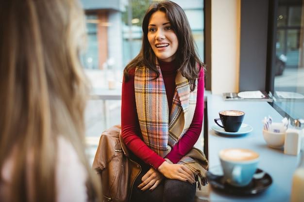 Ładni przyjaciele rozmawiają przy kawie