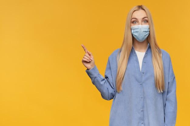 Ładnie wyglądająca kobieta, piękna dziewczyna o długich blond włosach. noszenie niebieskiej koszuli i medycznej maski na twarz. patrząc w kamerę i wskazując w lewo na miejsce na kopię, odizolowane na pomarańczowym tle