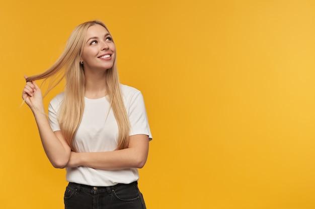 Ładnie wyglądająca kobieta, piękna dziewczyna o długich blond włosach. ubrana w białą koszulkę i czarne dżinsy. koncepcja ludzi i emocji. oglądanie w prawo w przestrzeni kopii, odizolowane na pomarańczowym tle