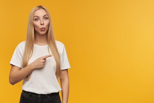 Ładnie wyglądająca kobieta, piękna dziewczyna o długich blond włosach. ubrana w białą koszulkę i czarne dżinsy. patrząc w kamerę i wskazując w prawo na miejsce na kopię, odizolowane na pomarańczowym tle