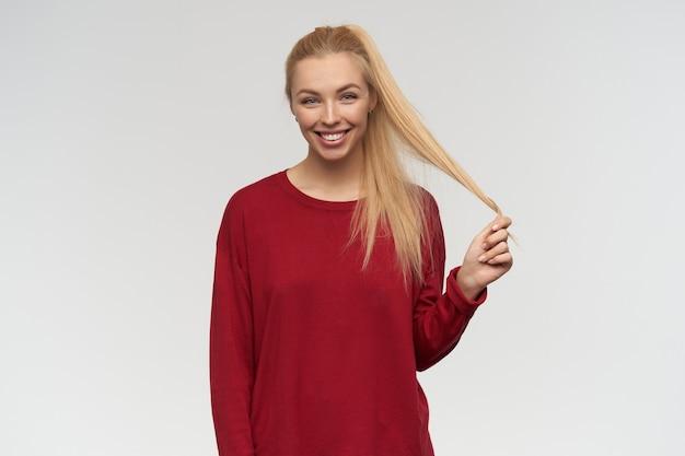 Ładnie wyglądająca kobieta, piękna dziewczyna o długich blond włosach. ubrany w czerwony sweter. koncepcja ludzi i emocji. oglądanie kamery, odizolowane na białym tle