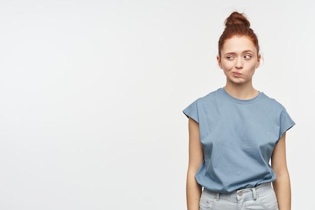 Ładnie wyglądająca kobieta, piękna dziewczyna o rudych włosach zebranych w kok. ubrana w niebieską koszulkę i dżinsy. zmruż oczy i obserwuj w lewo w miejsce na kopię, odizolowane na białej ścianie