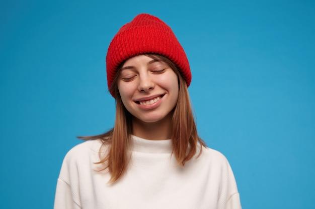 Ładnie wyglądająca kobieta, piękna dziewczyna z brunetką. na sobie biały sweter i czerwoną czapkę. ciepło, uśmiech z zamkniętymi oczami. zbliżenie, stojak na białym tle nad niebieską ścianą