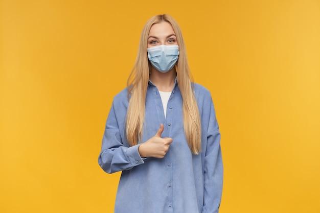 Ładnie wyglądająca kobieta, piękna dziewczyna z długimi blond włosami pokazuje kciuki do góry znak. noszenie niebieskiej koszuli i medycznej maski na twarz. pojedynczo na pomarańczowym tle