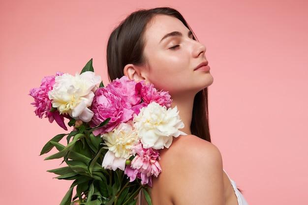 Ładnie wyglądająca kobieta, piękna dziewczyna z długimi brunetkami, zamkniętymi oczami i zdrową skórą. ma na sobie białą sukienkę i trzyma bukiet kwiatów tutaj z tyłu. stań odizolowany na pastelowej różowej ścianie