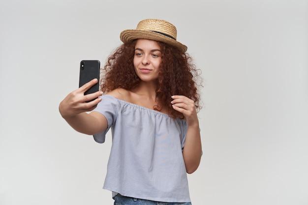 Ładnie wyglądająca kobieta, piękna dziewczyna z kręconymi rudymi włosami. na sobie bluzkę i kapelusz w paski z odkrytymi ramionami. robienie selfie na smartfonie. stań izolować na białej ścianie