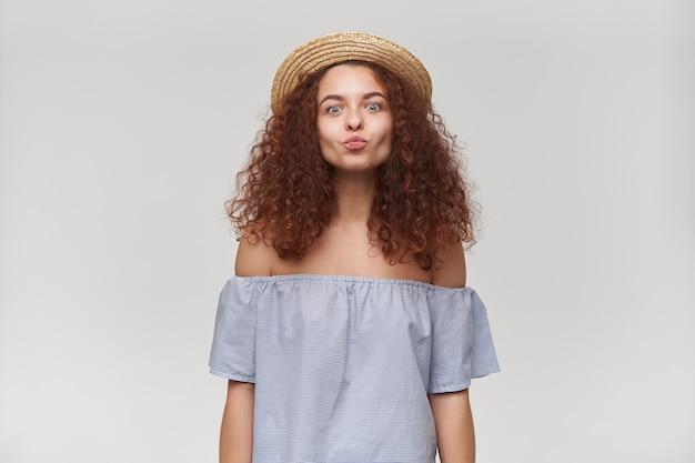 Ładnie wyglądająca kobieta, piękna dziewczyna z kręconymi rudymi włosami. na sobie bluzkę i kapelusz w paski z odkrytymi ramionami. wydymaj usta, całuj. pojedynczo na białej ścianie