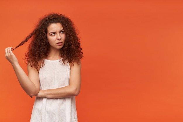 Ładnie wyglądająca kobieta, piękna dziewczyna z kręconymi rudymi włosami. ubrana w białą bluzkę z odkrytymi ramionami. zabawa kosmykiem włosów. oglądanie w prawo w miejsce na kopię, odizolowane na pomarańczowej ścianie