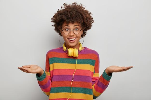 Ładnie wyglądająca kobieta unosi obie dłonie, trzyma miejsce na kopię, ma przyjazny wyraz twarzy, nosi okulary, swobodny sweter, patrzy bezpośrednio w kamerę, używa słuchawek