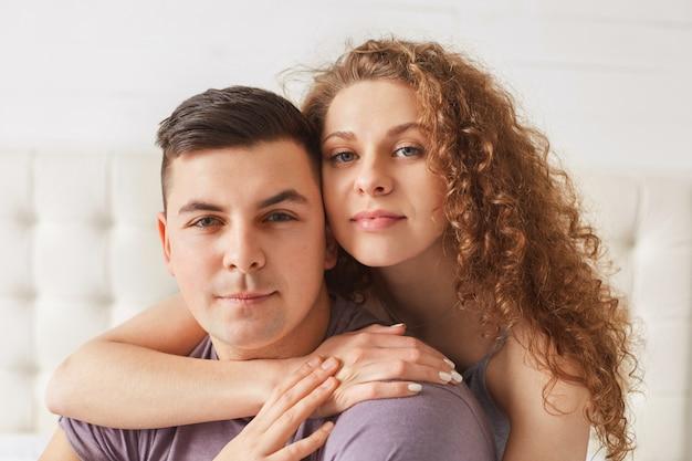 Ładnie wyglądająca młoda kobieta przytula swojego przystojnego chłopaka, pozuje razem przed domowym wnętrzem, spędza dzień wolny w domu
