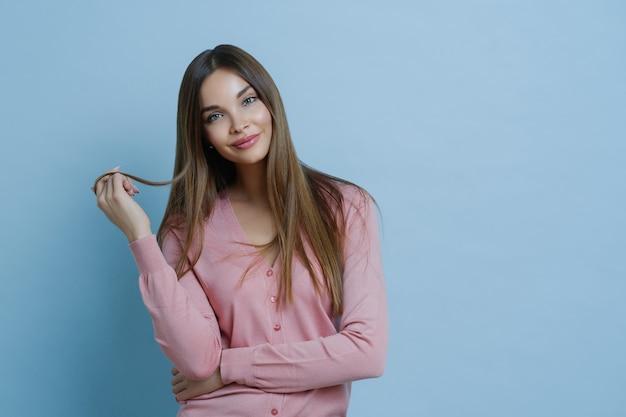Ładnie wyglądająca młoda kobieta w talii ma piękne długie włosy, przechyla głowę, ubrana w swobodny sweter, ma idealnie czystą skórę