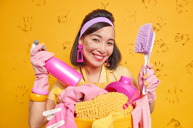 Ładnie wyglądająca wesoła azjatka uśmiecha się radośnie trzyma pędzel i spray do mycia płynów czyszczących zajęta praniem nosi ochronne gumowe rękawiczki ma brudną twarz i ubrania pozuje w pomieszczeniu.