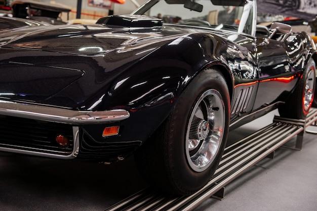 Ładnie wyglądający stary samochód sportowy stojący na specjalnym stoisku w pomieszczeniu na pokazie samochodowym