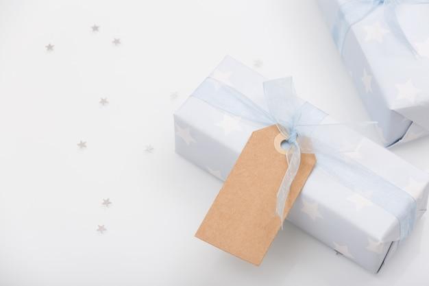 Ładnie zapakowane prezenty w papier z gwiazdkami i jasnoniebieską wstążką oraz makieta na białym stole