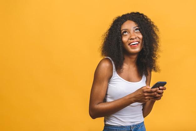 Ładny afroamerykanin czarny dziewczyna z falowanymi włosami trzymając w rękach telefon na czacie w sieci