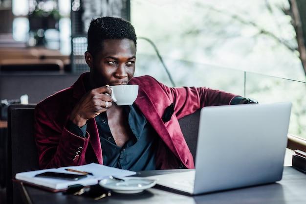 Ładny, afrykański biznesmen robi sobie przerwę na kawę w kawiarni i pracuje na swoim laptopie.