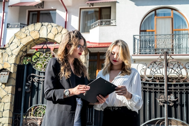 Ładny agent nieruchomości omawiający nieruchomość z klientką na świeżym powietrzu w pobliżu nowego domu. koncepcja sle