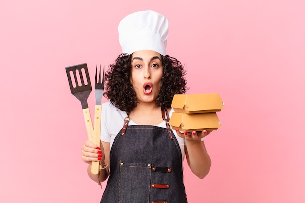 Ładny arabski szef kuchni z grilla z burgerami na wynos?