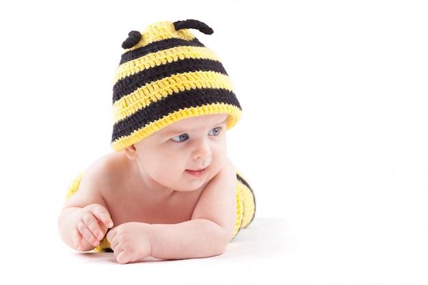 Ładny atrakcyjny chłopczyk w stroju pszczoły leży na brzuchu