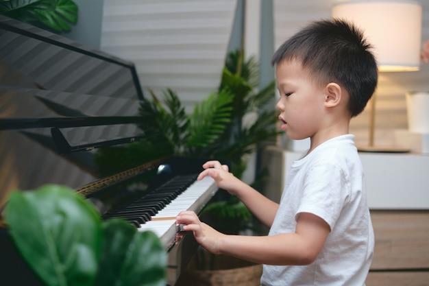 Ładny azjatycki chłopiec gra na pianinie