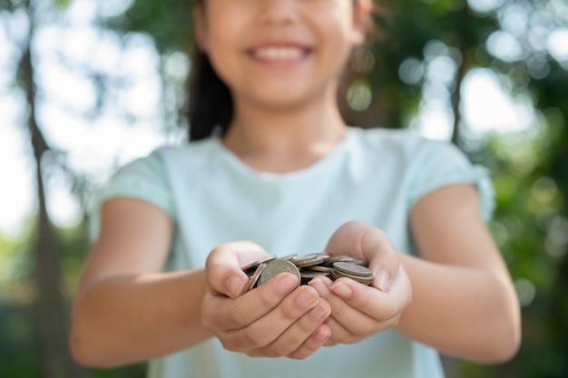 Ładny azjatycki mała dziewczynka gra z monety pieniądze, dziecko ręka trzyma pieniądze. dziecko oszczędza pieniądze w skarbonce. dziecko liczy swoje zapisane monety, dzieci uczą się o przyszłej koncepcji.
