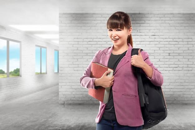 Ładny azjatykci żeński student collegu z książką