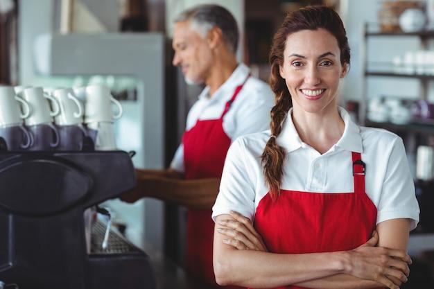 Ładny barista ono uśmiecha się przy kamerą z kolegą behind