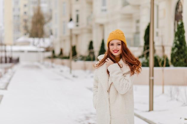 Ładny biały kobieta pozowanie w zimowy dzień. plenerowe zdjęcie zadowolonej rudej pani w długim płaszczu.