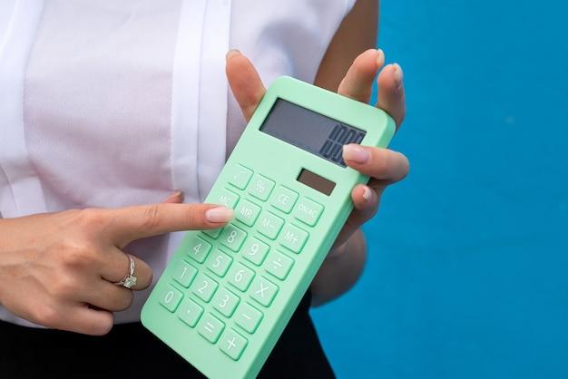 Ładny biznes kobieta trzymać kalkulator w niebieskiej ścianie