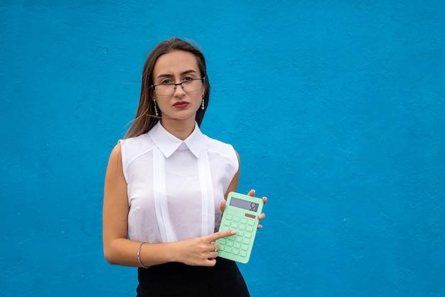 Ładny biznes kobieta trzymać kalkulator w niebieskim tle