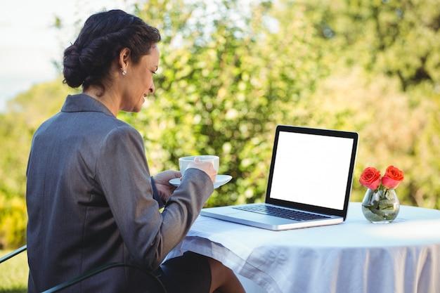 Ładny bizneswoman ma kawę i używa laptop