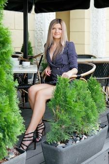 Ładny bizneswoman pije cappuccino przy caffe tarasem