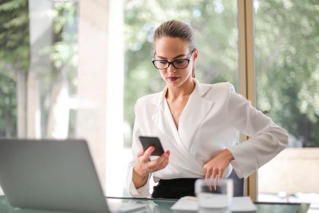 Ładny bizneswoman sprawdza jej telefon