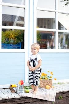 Ładny blond chłopiec w kombinezonie i białej koszulce stoi na werandzie drewnianego wiejskiego domu w jesienny dzień. odpoczywaj w naturze. koncepcja dzieciństwa. żniwny. mały rolnik. zdrowy styl życia rodziny