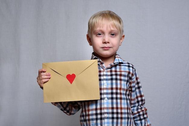 Ładny blond chłopiec z kopertą z czerwonym sercem
