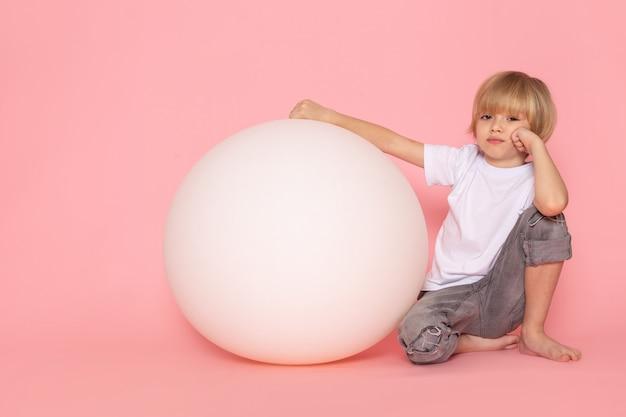 Ładny blond chłopiec z przodu w białej koszulce bawi się okrągłą białą piłką na różowej przestrzeni